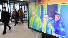 Правителствени служители минават край термокамера, която проверява температурата на телата на посетители в правителствена сграда в Седжонг, Южна Корея, като мярка срещу коронавируса.