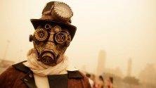 Участник в карнавал в Тенерифе, Канарските острови, който се провежда въпреки гъстите облаци от прах и пясък, донесени от Сахара.