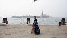 Жена в традиционен костюм за карнавала във Венеция се разхожда из града. Броят на туристите, идващи в града за карнавала, падна значително заради коронавируса.