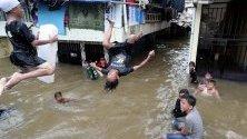 Деца скачат във водите на наводнен квартал в Джакарта, Индонезия. Проливните дъждове потопиха мегаполиса под вода, която на места достига 150 см.