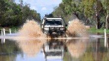 Кола минава през наводнена улица в Сейнт Джордж, Куийнсленд, Австралия, след излизането на река Балоун от коритото й с 12 метра заради проливни дъждове.