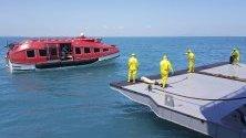 Служители в защитни костюми чакат акостирането на военен кораб-болница с пациенти, евакуирани от круизния кораб World Dream заради наличие на коронавирус.