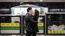 Двойка се целува със свалени маски срещу коронавируса докато чакат влак на гарата в Шанхай, Китай.