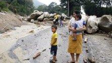Местни жители наблюдават свлачище в Пиедекуеста, Колумбия. Проливните дъждове засегнаха обширни райони на Андите и причиниха жертви сред населението.
