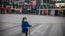Момченце с предпазна маска срещу коронавируса си играе на празен площад в търговски район в Пекин, Китай.