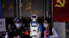 Робот помага на служителите при проверка на температурата на посетители в правителствена сграда в Гуанджоу, Китай.