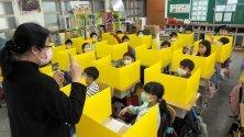 Ученици стоят зад ограничителни прегради, предпазващи от коронавируса, в основно училище в Тайпе, Тайван.