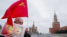 Комунист в Русия държи портрет на Сталин по време на честване на 67 години от смъртта му край Кремъл, Москва.