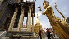 Туристи в предпазни маски срещу коронавируса посещават храма на Смарагдовия Буда в Банкок, Тайланд. Страната отчита спад на туристите с 6 милиона до най-ниското ниво от четири години.