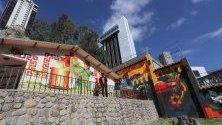 Боливийският творец Фреди Мамани позира до свои графити върху правителствена резиденция в Ла Пас, Боливия.