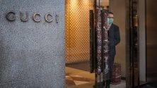 """Служител в магазин на """"Гучи"""" с предпазна маска в очакване на клиенти в Милано, Италия."""