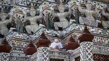 Китайски турист с предпазна маска срещу коронавируса подещава Уат Арун - Храмът на зората, в Банкок, Тайланд. Страната очаква спад на туристите до най-ниското ниво от четири години.
