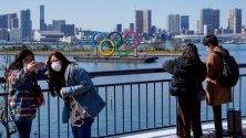 Туристи с предпазни маски позират пред олимпийските пръстени в Токио, Япония. Очаква се Олимпиадата да бъде отложена за края на годината.